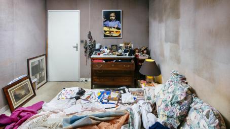 Makuuhuone, jossa on petaamaton sänky jolla on kirjoja, lipasto jonka ylin laatikko on auki ja seinällä taulu jossa on lapsi katsomassa jotain kuvaa.