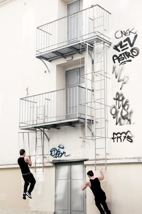 Vaalean rakennuksen seinässä on allekkain kolme ovea, joiden molemmilla puolilla menee tikkaat alas. Tikkaiden alimmilla askelmilla roikkuu kaksi miestä mustissa hihattomissa paidoissa ja mustissa housuissa.