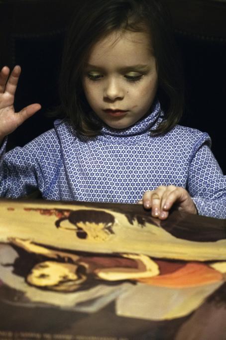 Lapsi katsoo jotain kuvaa josta hän pitää kiinni. Toinen käsi on kohotettuna vähän ylös.