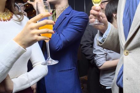 Hienosti pukeutuneita ihmisiä käsissään lasilliset oranssia juotavaa. Kuva on otettu niin että ihmisten päät ovat rajautuneet pois.