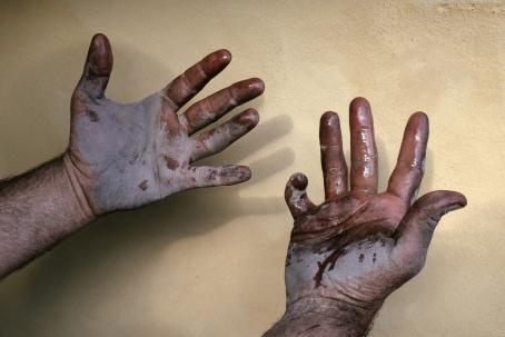 Ihmisen kädet kämmenpuoli ylöspäin. Kädet ovat likaiset ja märät.