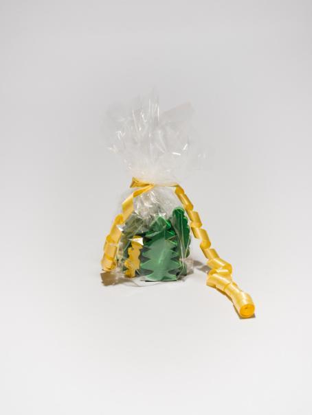 Valkoista taustaa vasten sellofaaniin pakattuna vihreitä, litteitä, kuusenmuotoisia esineitä. Ympärillä keltainen lahjanauha.