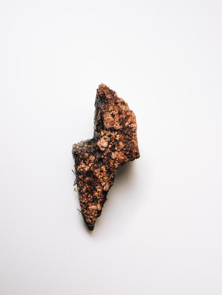 Pieni, multainen, salaman muotoinen punaisen ja oranssin sävyinen kivi.