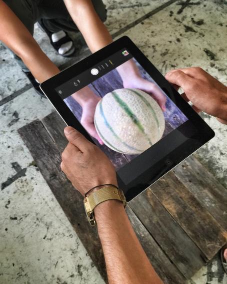 Joku ottaa padilla kuvaa melonista, jota toinen henkilö pitää käsissään pöydän yläpuolella.