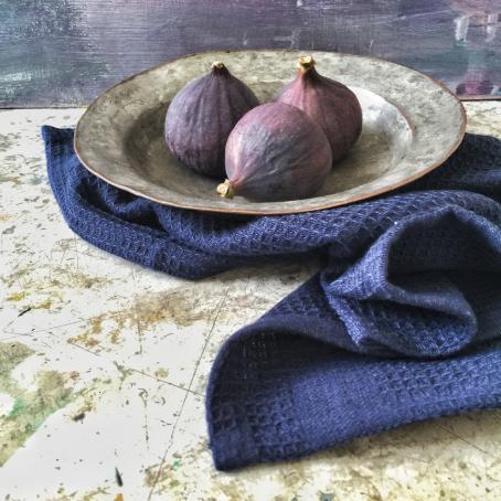 Pöydällä kulhossa on kolme pyöreää violettia viikunaa. Kulhon alla on sininen kangas levitettynä pöydälle.