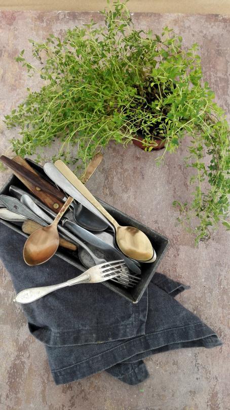Pöydällä on laatikko jossa on ruokailuvälineitä. Sen alla on taiteltuna tummansinistä kangasta oleva liina. Laatikon vieressä on purkissa vihreä kasvi.