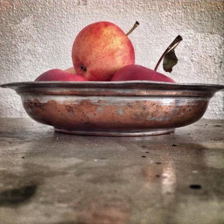 Pöydän tasosta kuvattu kulho, jossa on omenoita.