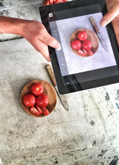 Pöydällä on kulhossa tomaatteja ja niiden vieressä veitsi. Joku ottaa niistä kuvaa padilla.