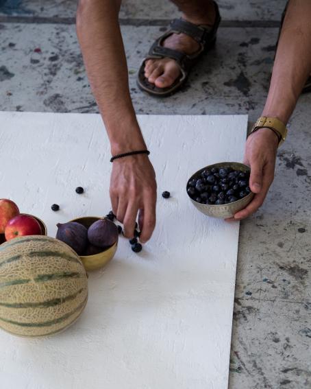 Lattialla on valkoinen alusta, jossa on kulhoissa hedelmiä. Kuvassa näkyy jonkun jalat ja kädet, hän laittaa alustalle kulhosta sinisiä marjoja.