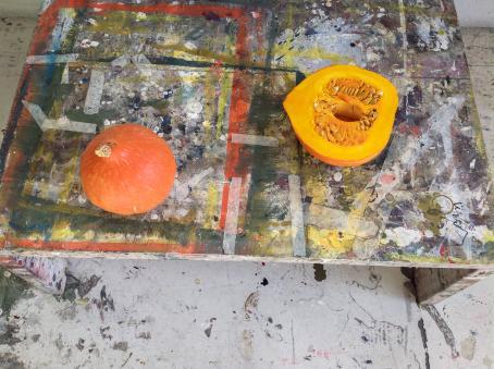Tahraisen pöydän päällä on oranssi kokonainen kurpitsa, sekä puolikas kurpitsa.