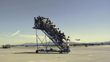 Lentokentällä olevat siirrettävät portaat ovat täynnä ihmisiä, mutta portaiden vieressä ei ole lentokonetta.