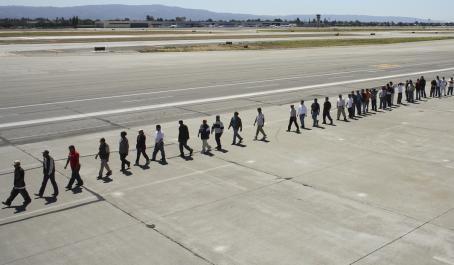 Ihmisiä kävelee pitkässä jonossa lentokentällä.