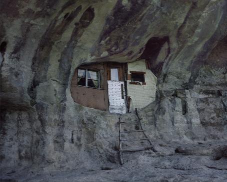 Kalliossa olevaan reikään tai luolaan on tehty seinä, ikkuna ja ovi. Ovelle menevät lyhyet tikkaat.
