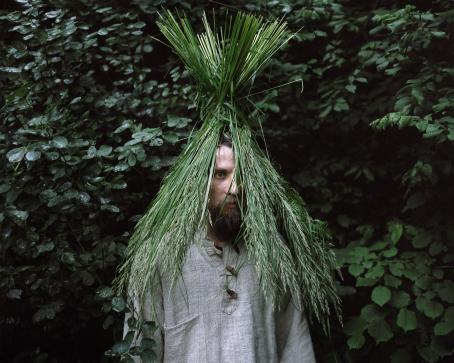 Mies, jonka päähän on laitettu tukku heiniä niin, että ne ovat kuin hänen hiuksensa. Takana näkyy vihreitä lehtiä.