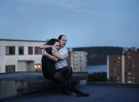 Mies ja nainen istuvat kerrostalon katolla ja halaavat toisiaan. Naisella on silmät kiinni ja hän hymyilee. Taustalla näkyy kerrostaloja, vettä ja metsää.
