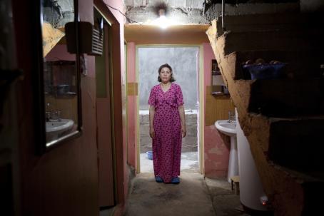 Nainen pinkissä mekossa seisoo ovensuussa huonokuntoisen näköisessä asunnossa. Hänen yläpuolellaan on hehkulamppu jossa ei ole varjostinta.