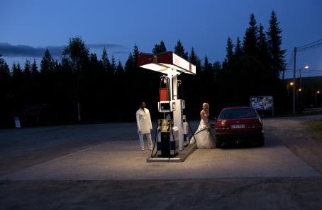 Pimeässä maisemassa valaistu bensa-asema, jossa häämekkoon pukeutunut nainen tankkaa punaista autoa. Hän katsoo vähän kauempana seisovaa ihmistä, jolla on valkoiset housut ja valkoinen pitkä paita.