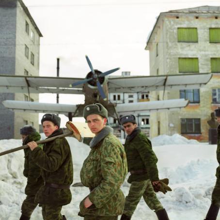 Armeijan asuihin pukeutuneita miehiä kävelee lumisella tiellä, yhden olalla on lumilapio. Heidän takanaan on potkurikone kerrostalojen välissä.