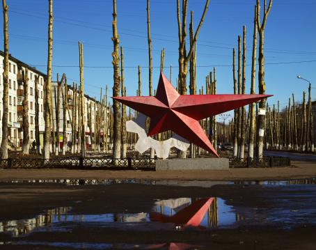 Monumentti, jossa on punainen tähti jonka sakarat ovat eripituisia, ja sen vieressä valkoinen hammasratas. Sen takana on lehdettomiä puita ja taaempana kerrostaloja.