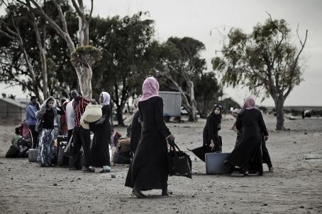 Tummaihoisia ihmisiä ulkona, naisilla on huivit päässä. Maassa on paljon matkalaukkuja ja heillä on myös käsissään laukkuja ja tavaroita.