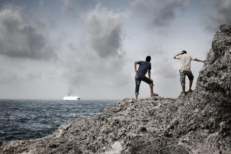 Kaksi ihmistä seisoo rantakalliolla selin kameraan. Toinen nojaa pystysuoraan kallioon ja toinen jalkoihinsa. Kauempana merellä menee risteilyalus.