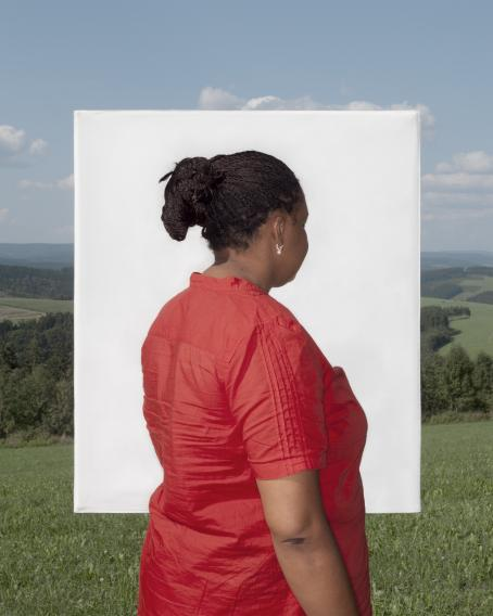 Tummaihoinen nainen punaisessa mekossa katsoo poispäin. Hänen taustallaan on valkoinen suorakulmio, ja sen takana näkyy vihreää peltomaisemaa.