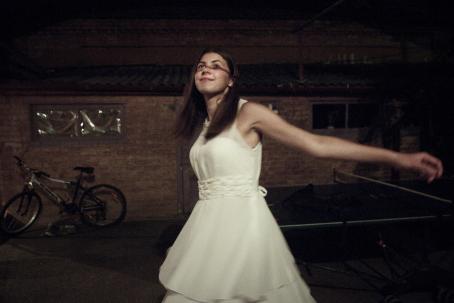 Tyttö valkoisessa mekossa on kädet levällään ja hymyilee. Hänen kasvoilleen lankeaa vaakasuora varjo vähän silmien alapuolelle.