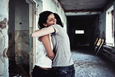 Kaksi ihmistä halaavat toisiaan. He ovat ränsistyneen näköisen rakennuksen käytävällä. Toinen heistä hymyilee leveästi, toisen kasvoja ei näy.