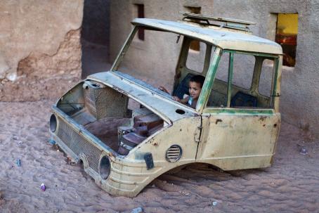 Auton runko, josta puuttuu renkaat, ikkunat ja moottori. Autossa istuu pikkupoika.