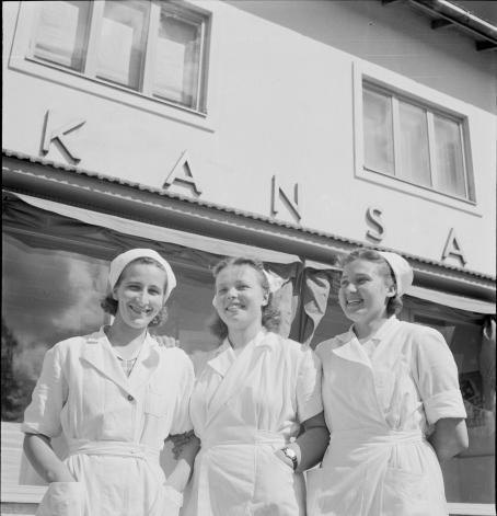 """Kolme nuorta naista valkoisissa asuissa ja lakeissa. Takana olevan rakennuksen seinässä lukee """"Kansa""""."""