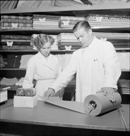 Mies mittaa rullasta käärepaperia tiskillä. Vieressä nainen katsoo. Heidän takanaan on hyllyillä paljon kankaita.