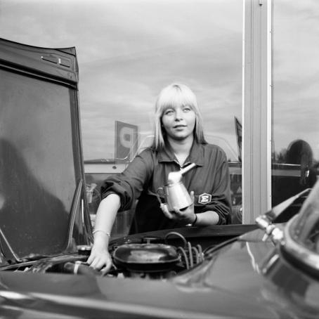 Auton konepelti auki. Nainen tekee moottorille jotain ja hänellä on kädessään jokin astia. Takana olevaan ikkunaan heijastuu P-paikan kyltti.