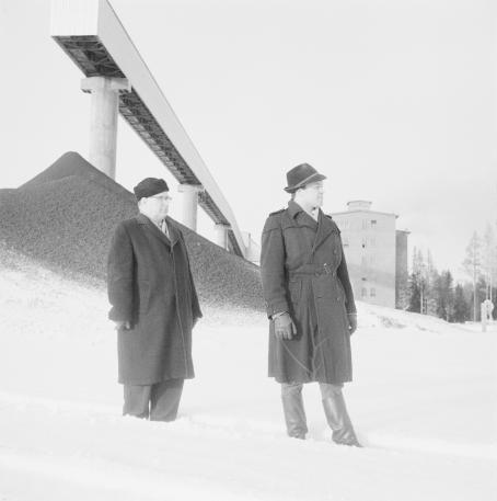 Kaksi miestä seisoo talvivaatteissa lumihangessa. Heidän takanaan näkyy kasa soraa tai jotain muuta ainetta ja pitkä, kapea pylväiden varassa oleva taso.