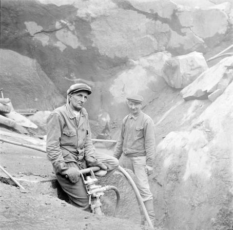 Kaksi miestä kallioiden ympäröimänä. Toinen pitelee käsin käytettävää poraa.