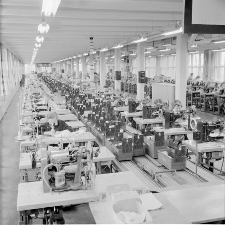 Näkymä isosta tehtaasta, missä työntekijät ompelevat ompelukoneilla.