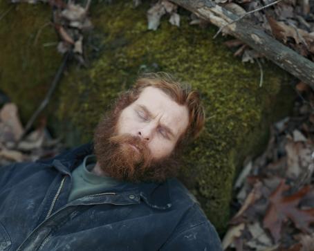 Mies jolla on oranssinruskeat hiukset ja parta makaa metsässä pää sammalen peittämällä kivellä. Hänellä on silmät kiinni ja päällä likainen sininen takki.