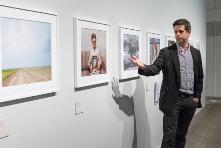 Mies osoittaa kädellään näyttelyssä olevaa taulua, jossa on kuva vanhasta naisesta istumassa sohvalla taulu sylissään.