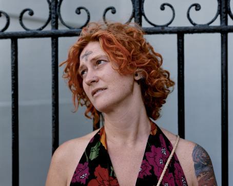 Nainen jolla on oranssit, kiharat hiukset, istuu nojaten metalliseen aitaan. Hänellä on otsassaan mustalla tehty risti ja olkavarressa tatuointi.