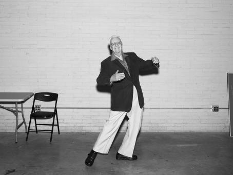 Mustavalkoisessa kuvassa vanha mies on tanssivassa asennossa, hän on laittanut kätensä näkymättömän ihmisen ympärille.