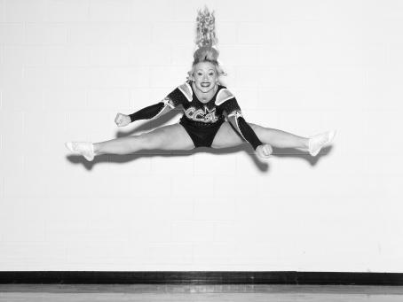 Mustavalkoisessa kuvassa nainen cheerleaderin asussa on hypännyt ilmaan ja hänen jalkansa ovat levällään sivuilla. Hänen poninhäntänsä on pystyssä ja hän hymyilee leveästi. Asussa lukee LCA.