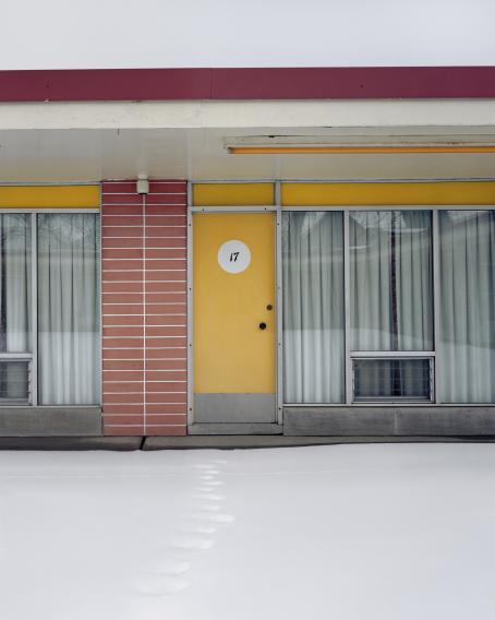 Rakennuksen seinusta. Korkeiden ikkunoiden eteen on vedetty haaleanvihreät pitkät verhot. Ovi on keltainen ja siinä on numero 17. Lumessa näkyvät yhdet jalanjäljet ovelle.