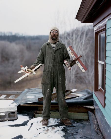 Mies vihreässä haalarissa seisoo talon edustalla. Hänellä on parta, pyöreät silmälasit ja vaalea huppulakki. Hänellä on kummassakin kädessä puinen pieni lentokone. Takana näkyy lehdetöntä risukkoa.