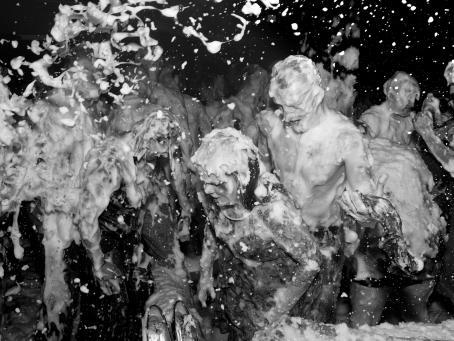 Mustavalkoisessa kuvassa vähäpukeiset ihmiset ovat vaahdon peitossa ja heittelevät sitä toistensa päälle.