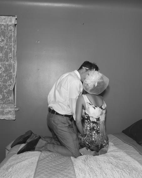 Mustavalkoisessa kuvassa sängyllä istuu selin nainen mekossa ja hatussa. Hänen vieressään sängyllä on polvillaan mies, jonka kasvot ovat lähellä naisen kasvoja ja ne jäävät naisen hatun taakse. Miehen korvan takana on tupakka.