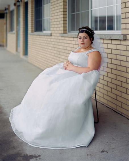 Nainen valkoisessa häämekossa ja huntu päässä istuu tiilisen talon edessä, kädet ristissä sylissä.