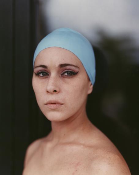 Nainen, jolla on päässä sininen panta. Tausta on sumea.