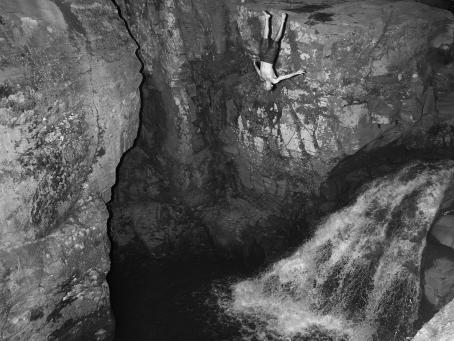 Mustavalkoisessa kuvassa mies on kallion vieressä ylösalaisin ilmassa, kuin hän olisi juuri hypännyt. Alhaalla on vesiputous.