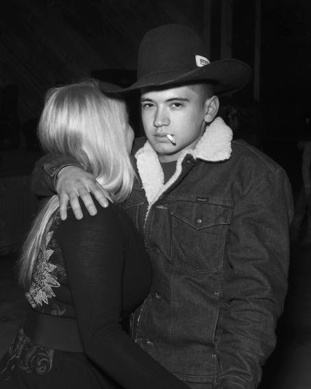 Mustavalkoisessa kuvassa mies karvavuorisessa farkkutakissa ja cowboy-hatussa, tupakka suussa. Hän halaa yhdellä kädellä vaaleahiuksista naista, naisen kasvot eivät näy kuvassa.