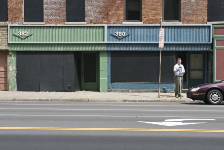 Katunäkymä. Tien toisella puolella olevien talojen ikkunat on peitetty mustalla levyllä. Mies on maksamassa pysäköintimaksua parkkimittariin.