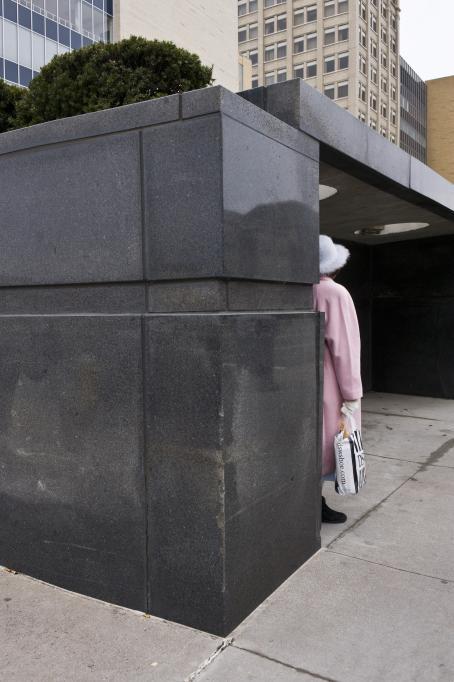Tummasta kivestä tehty bussipysäkki, jonka sivuilla olevat pylväät ovat paksut. Pylvään takana seisoo nainen vaaleanpunaisessa takissa.